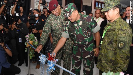 Officers of the Indonesian, Malaysian and Philippines militaries cut a ribbon at a ceremony announcing new joint patrols by the three countries.