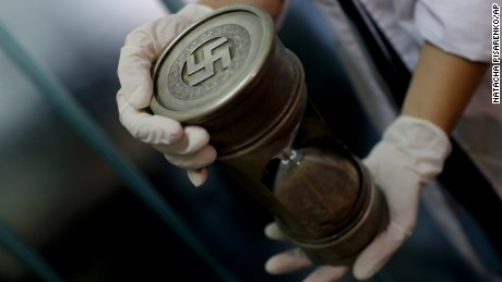 A member of the federal police holds an hourglass with Nazi markings at the Interpol headquarters in Buenos Aires, Argentina, Friday, June 16, 2017. In a hidden room in a house near Argentina's capital, police discovered on June 8th the biggest collection of Nazi artifacts in the country's history. Authorities say they suspect they are originals that belonged to high-ranking Nazis in Germany during World War II. (AP Photo/Natacha Pisarenko)