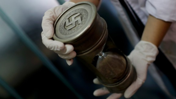 A member of the federal police holds an hourglass with Nazi markings at the Interpol headquarters in Buenos Aires, Argentina, Friday, June 16, 2017. In a hidden room in a house near Argentina