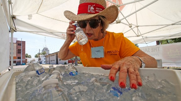 Volunteer Jackie Rifkin tries to keep cool June 19 at she works at a Salvation Army station to help people stay hydrated in Phoenix.