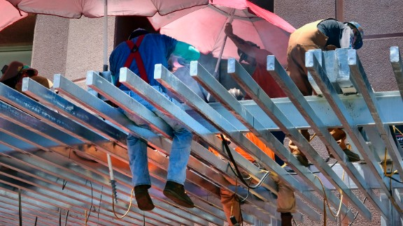 Construction workers try to shade themselves from the direct sun while welding a steel awning in Los Angeles on June 19.