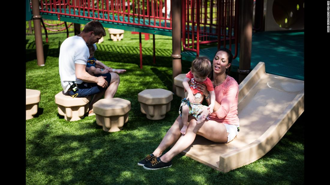 Nicole McDonald plays with her son Anias as Christian McDonald holds Jadon on a playground outside Blythedale Children's Hospital.