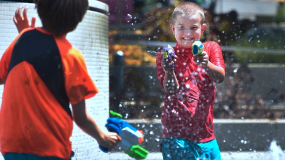 Boys cool off with water guns in downtown Los Angeles on Monday, June 19.