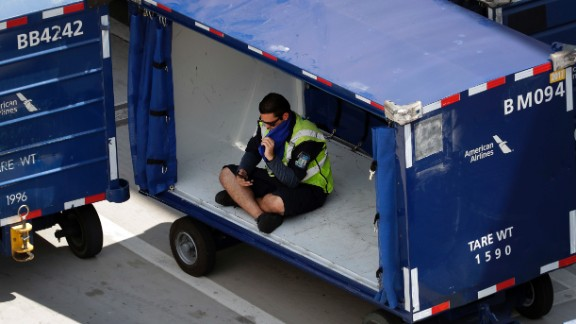 An American Airlines grounds crew member sits in a luggage cart to avoid the heat in Phoenix on June 20.