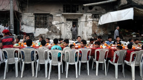 Children sit at a table as they wait for iftar.