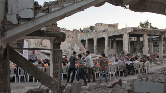 Douma residents eat amid bombed-out buildings.