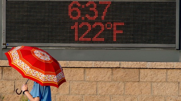 PHOENIX, AZ - JUNE 20:  A pedestrian uses an umbrella to get some relief from the sun as she walks past a sign displaying the temperature on June 20, 2017 in Phoenix, Arizona.  Record temperatures of 118 to 120 degrees were expected on Tuesday for the Phoenix-metro area.  (Photo by Ralph Freso/Getty Images)