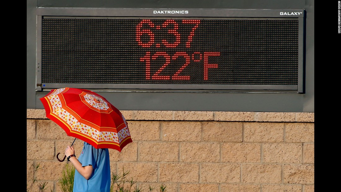 A pedestrian in Phoenix uses an umbrella to get some relief from the sun on June 20.