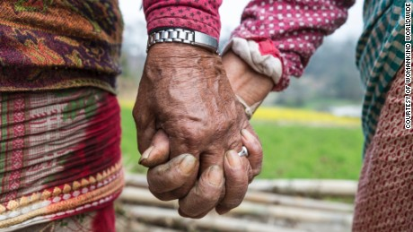 Widows hold hands in Chapaguan, Nepal