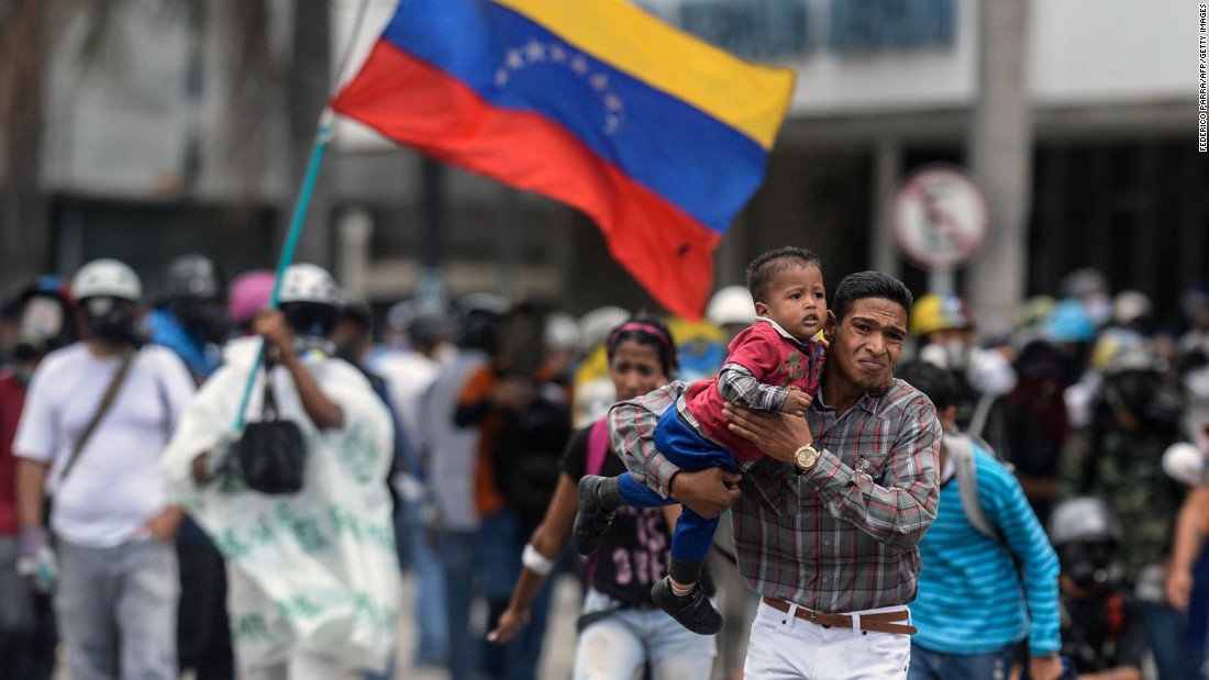 People flee during a clash between opposition demonstrators and riot police in Caracas on June 19.
