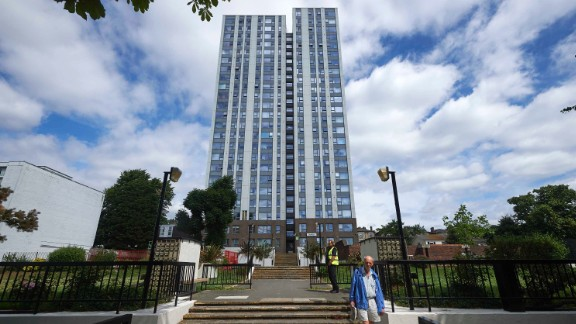 A resident walks down the steps in front of the Dorney residential tower block in north London on June 23, 2017.Tower blocks housing thousands of people across England are being urgently tested to check if their outer coverings pose a serious fire risk following the Grenfell Tower disaster, with nearly a dozen already testing positive for combustible material. 11 buildings have already been confirmed by the Government to have combustible cladding including five buildings on the Chalcots Estate in north London. Camden Council said in a statement that the external cladding panels on the five blocks at the estate did not satisfy their independent laboratory testing and that they would immediately begin preparing to remove them. / AFP PHOTO / NIKLAS HALLE'N        (Photo credit should read NIKLAS HALLE'N/AFP/Getty Images)