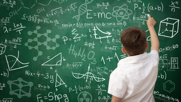 Back view of schoolboy writing math formula on green  blackboard; Shutterstock ID 329564411; PO: CNN Photos Health Request