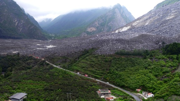 Vehicles and people line a road leading to the site of a landslide near Xinmo on June 24.
