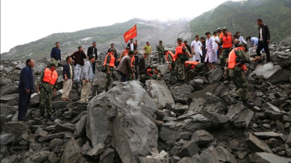 Emergency personnel swarm the area of landslide looking for survivors on June 24.