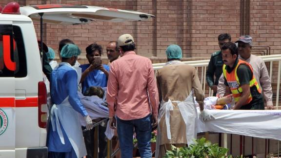 Pakistani paramedics bring a burn victim to a hospital in Multan, Pakistan.