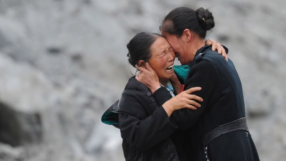 Two people cry among the rubble on June 25.