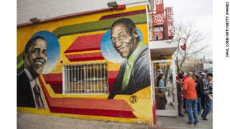 People walk past a mural of comedian Bill Cosby on the side of Ben's Chili Bowl in Washington, D.C. The mural has since been repainted.