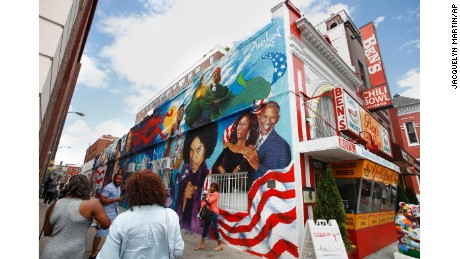 People take pictures of the new mural at Ben's Chili Bowl, Friday, June 23, 2017, in Washington.