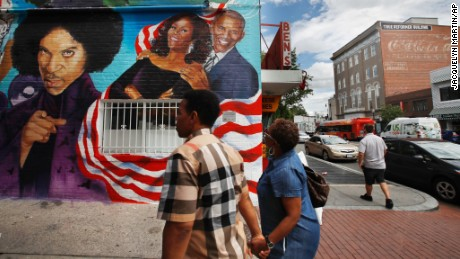 People visit a new mural at Ben's Chili Bowl, Friday, June 23, 2017, in Washington.