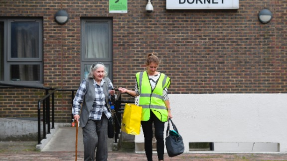 A council worker helps a resident leave Dorney Tower residential block on the Chalcots Estate in north London on June 25, 2017.