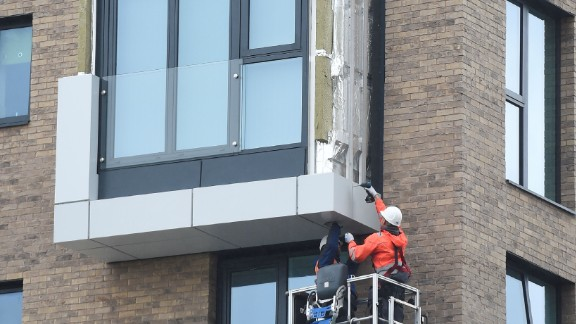 Workers remove panels of external cladding from the facade of a building in the Wythenshawe area of Manchester, northwest England.