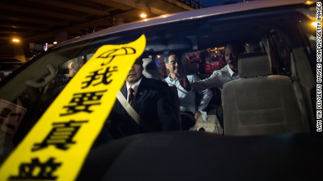"A banner with the Chinese characters ""I want true universal suffrage"" placed on the windscreen of a car carrying Hong Kong leader CY Leung."