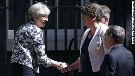 Theresa May (L) shakes hands with DUP leader Arlene Foster.