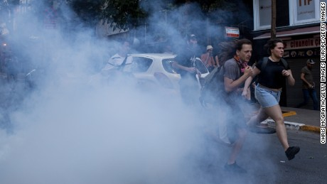 LGBT supporters run from tear gas fired by police after attempting to march to Taksim Square.