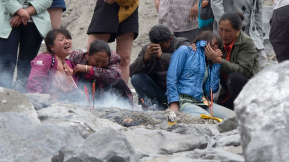 Family members grieve at the site of a landslide in Xinmo village on Sunday, June 25, 2017.