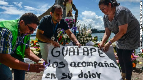 Survivors and locals place candels and flowers in tribute of the victims of the sank tourist boat 'Almirante', in the Reservoir of Penol in Guatape municipality in Antioquia, northwestern Colombia on June 26, 2017.  Divers combed the murky depths of a Colombian reservoir Monday for the bodies of missing passengers from a pleasure boat that sank, killing seven people, as anxious relatives waited on the shore for news of their loved ones. / AFP PHOTO / JOAQUIN SARMIENTO        (Photo credit should read JOAQUIN SARMIENTO/AFP/Getty Images)