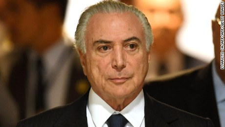 Brazilian President Michel Temer (C) arrives to the signing ceremony of a decree that fees differential prices for payment in cash and with credit card at the Planalto Palace in Brasilia, on June 26, 2017.  Temer faces his own crisis with the prosecutor general expected to request formal corruption charges against the president Monday or Tuesday. / AFP PHOTO / EVARISTO SA        (Photo credit should read EVARISTO SA/AFP/Getty Images)