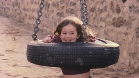 Lindsey Averill, around 4 years old, playing in a tire swing.