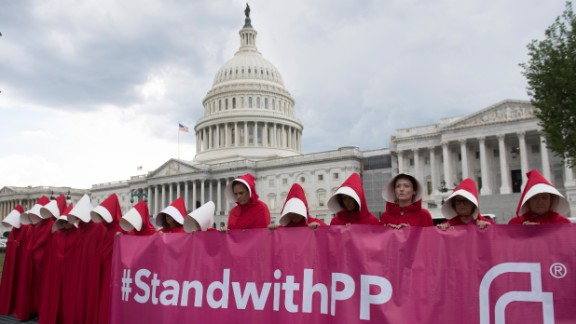 """Supporters of Planned Parenthood dressed as characters from """"The Handmaid's Tale,"""" hold a rally as they protest the US Senate Republicans' healthcare bill outside the US Capitol in Washington, DC, June 27, 2017. / AFP PHOTO / SAUL LOEB        (Photo credit should read SAUL LOEB/AFP/Getty Images)"""