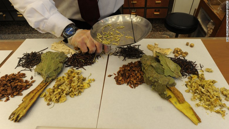 Workers at a traditional chinese medicine store prepare various dried items at a shop in Hong Kong.