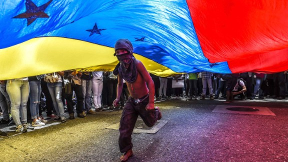 A boy runs under a national flag during a June 27 protest in Caracas.