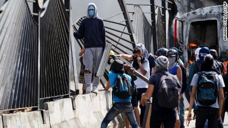 Protesters tear down a fence of the La Carlota Air Base during a protest on the Francisco Fajardo highway, outside in Caracas, Venezuela, Friday, June 23, 2017. More than 70 people have been killed during almost 90 days of protests seeking President Nicolas Maduro's removal. (AP Photo/Ariana Cubillos)