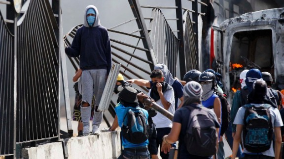 Protesters tear down a fence at the La Carlota airbase outside Caracas on Friday, June 23. A soldier shot a demonstrator through the fence at the base on the previous day, killing him.