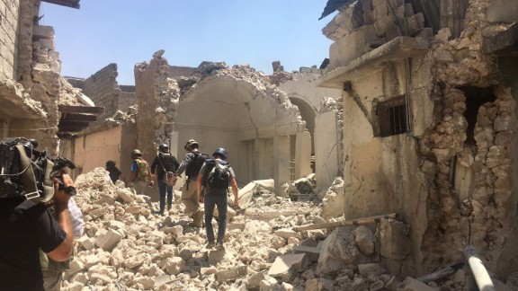 Journalists trudge through rubble escorted by Iraqis counter terror service to see recent gains.