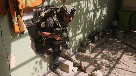 A member of the Iraqi counterterrorism service secures a building as troops push toward Mosul