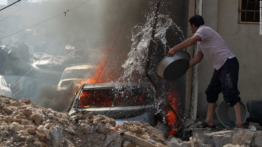 An Iraqi man tries to extinguish a burning car during fighting in Mosul's western Rifai neighborhood on Tuesday, May 16.