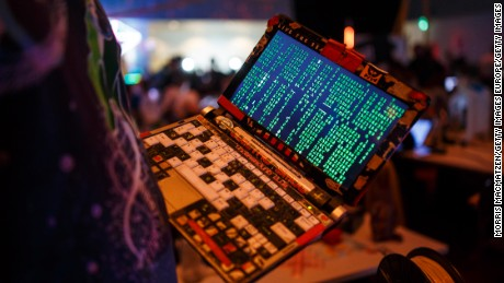 HAMBURG, GERMANY - DECEMBER 27: A participant poses with his laptop during the 33rd Chaos Communication Congress on its opening day on December 27, 2016 in Hamburg, Germany. The annual event is bringing together 12,000 computer hackers and activists who will meet over the next four days to share expertise and discuss topics related to the society and the digital world. (Photo by Morris MacMatzen/Getty Images)
