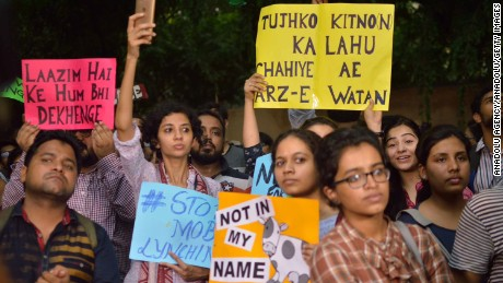 Protestors hold up signs in New Delhi.