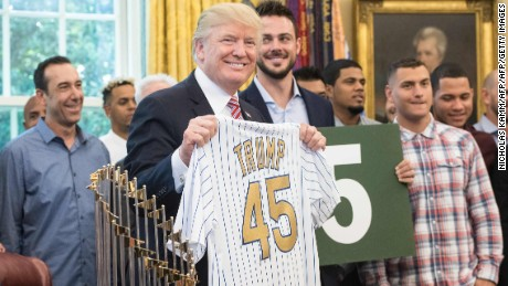 US President Donald Trump poses with a jersey given to him by members of the Chicago Cubs baseball team in the Oval Office at the White House in Washington, DC, on June 28, 2017. / AFP PHOTO / NICHOLAS KAMM        (Photo credit should read NICHOLAS KAMM/AFP/Getty Images)