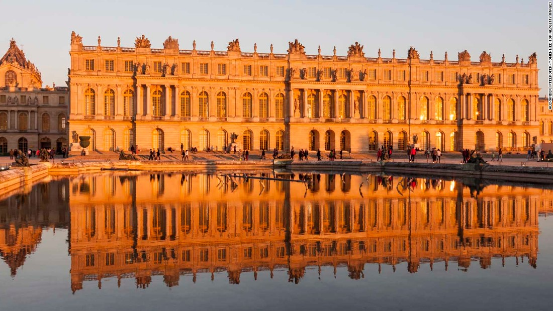 Versailles seen reflected in a pool at sunset.