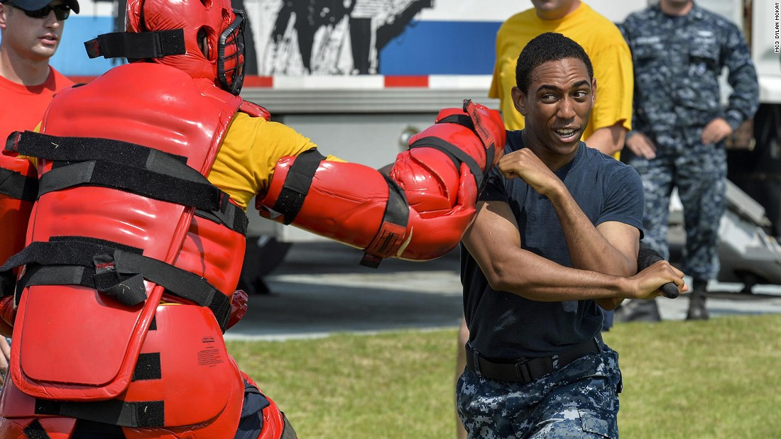 Navy Petty Officer 2nd Class Sean Morin fights off a simulated attacker after being exposed to oleoresin capsicum, or pepper spray, as part of security training in Yokosuka, Japan, on June 23.