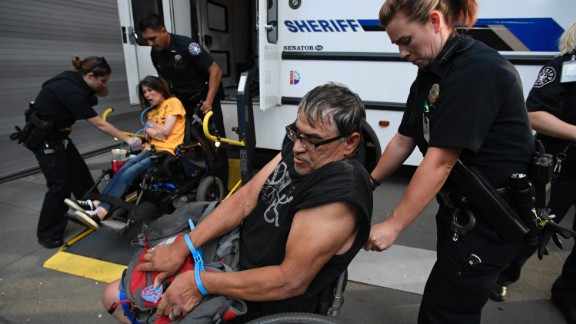 "DENVER, CO - JUNE 29: ADAPAT protesters Lonnie Smith (L) and Dawn Russell are loaded in to the Denver Sheriffs van after getting arrested from Senator Corey Gardner's office on June 29, 2017 downtown Denver, Colorado. Protesters were chanting ""Rather go to jail than to die without medicaid"" and free our people"". (Photo by John Leyba/The Denver Post via Getty Images)"