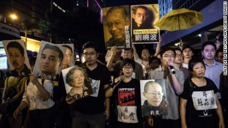 Pro-democracy supporters display posters (top) of Chinese dissident Liu Xiaobo during a protest march towards the venue where China's President Xi Jinping was attending a variety show in Hong Kong on June 30, 2017. Tight security contained protesters in Hong Kong Friday night as China's President Xi Jinping led lavish celebrations to mark 20 years since the politically divided city was handed back to China by Britain. / AFP PHOTO / DALE DE LA REY        (Photo credit should read DALE DE LA REY/AFP/Getty Images)