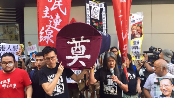 Hong Kong lawmaker Leung Kwok-hung (right) at a pro-democracy rally Saturday. Protesters were prevented from leaving the venue by pro-China counter demonstrators.