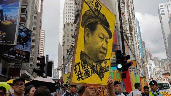 A protester raises a poster with Chinese President Xi Jinping