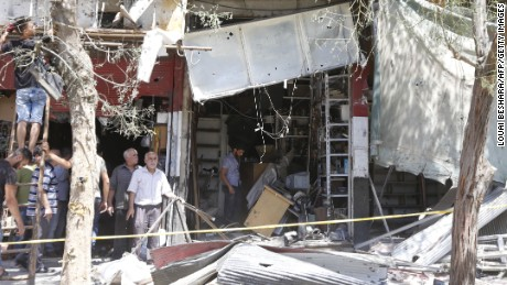 Syrians inspect the damage at the site of a suicide bomb attack in the capital Damascus' eastern Tahrir Square district.